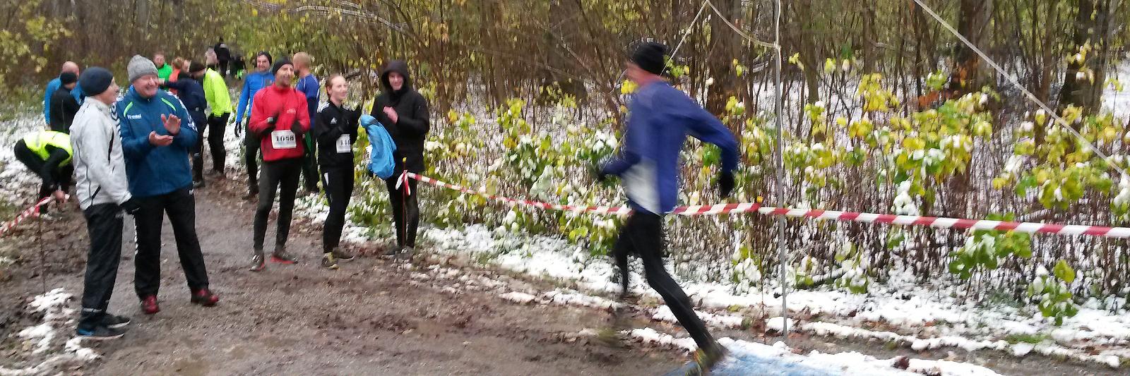 Løber i fuld fart passerer målstregen i mudder og sne