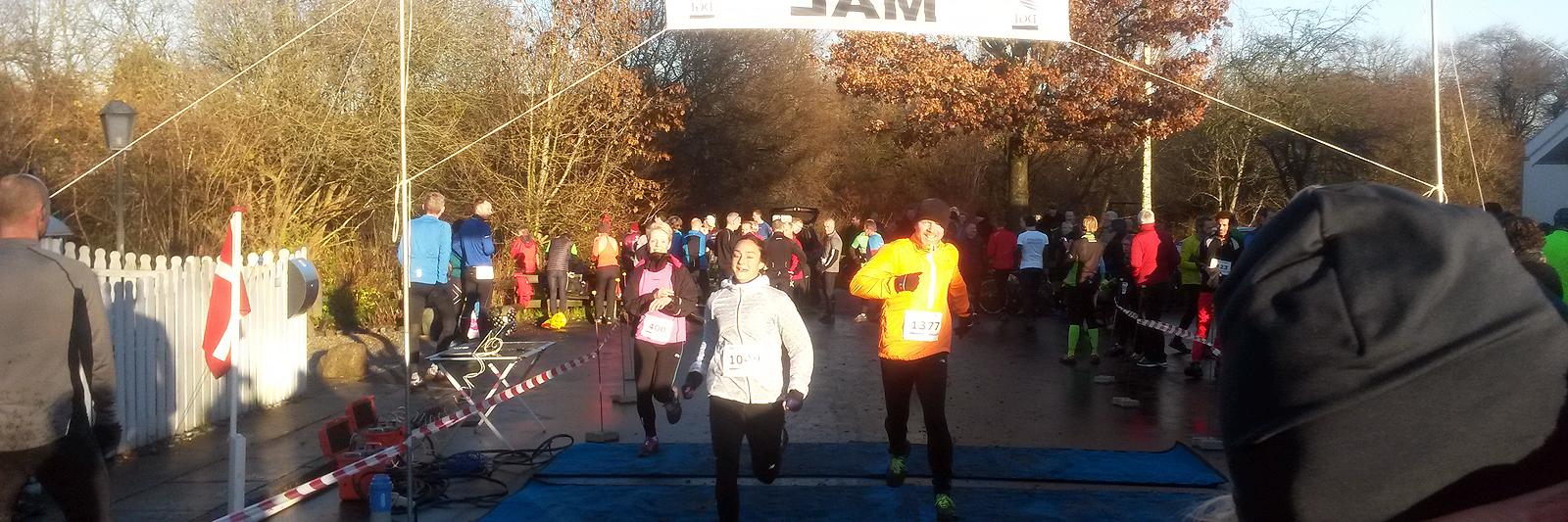3 løbere i lange bukser løber om kap under mål-banner i skarp sol med skov i baggrunden